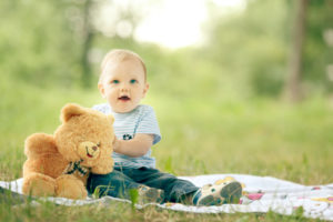little boy playing with a teddy bear in the grass